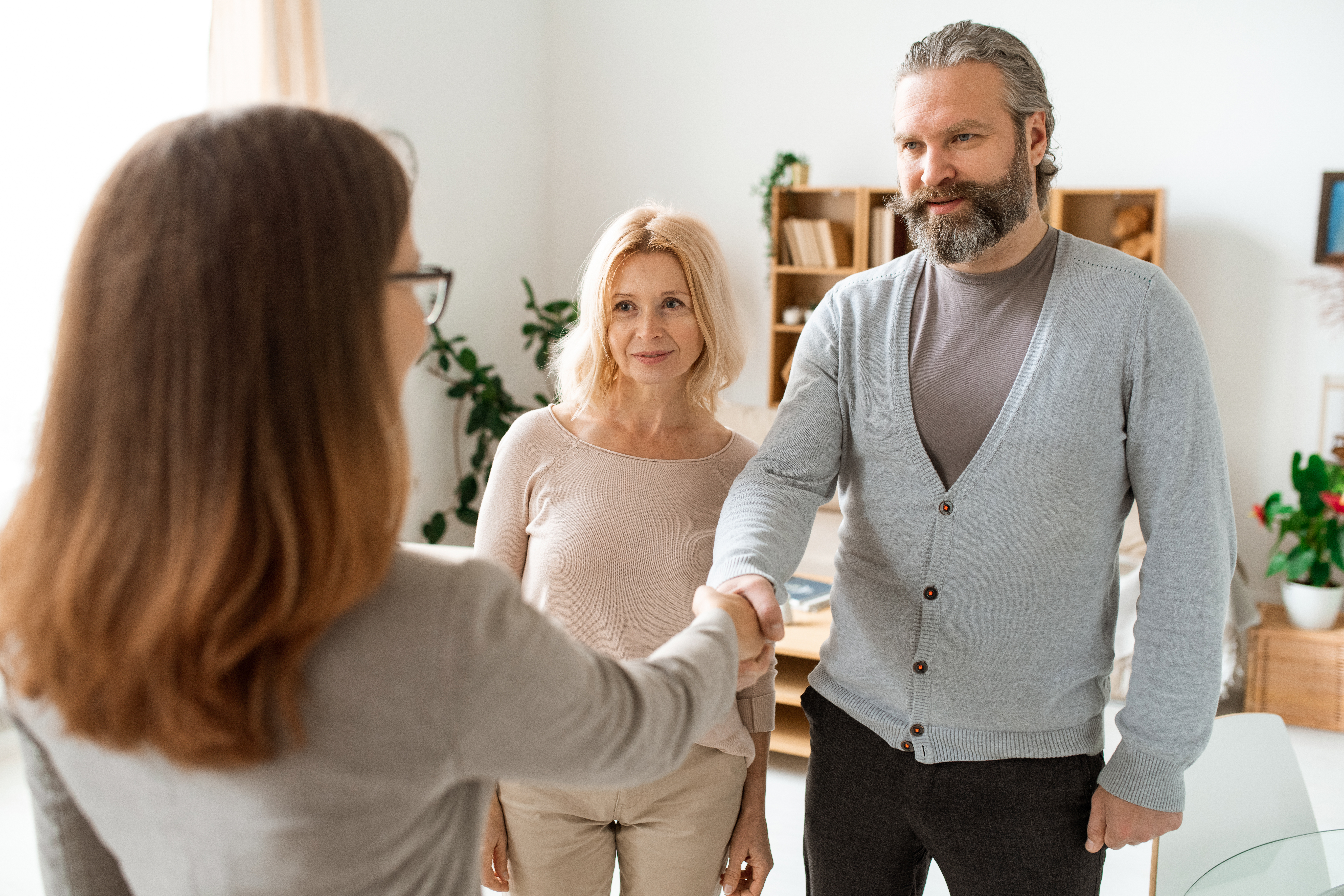 mature-casual-couple-greeting-their-real-estate-ad-BLUWRSK.jpg